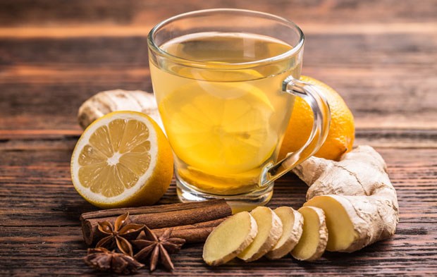 Cup of ginger tea with lemon on wooden table