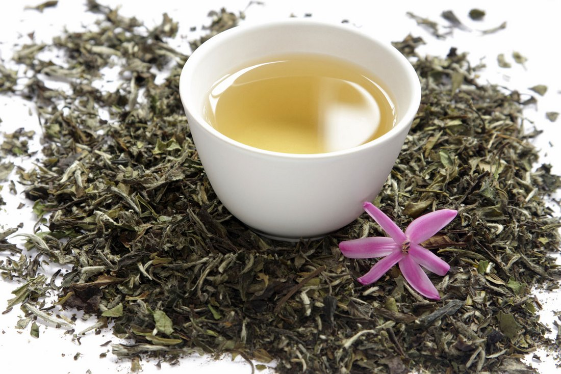 Cup of white tea with dry leaves